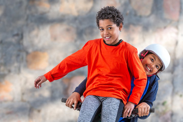 6 and 10 years old boys riding a bicycle over an old wall