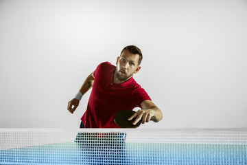 Wall Mural - Aspiring. Young man plays table tennis on white studio background. Model plays ping pong. Concept of leisure activity, sport, human emotions in gameplay, healthy lifestyle, motion, action, movement.