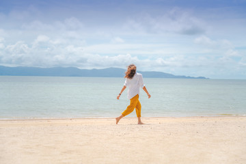 Young beautiful woman in a white shirt and yellow pants runs joyfully on the beach along the sandy shore of a tropical sea