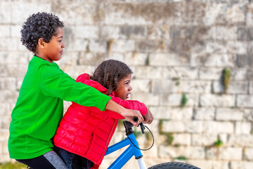 6 and 10 years old girl and boy riding a bicycle looking to an old wall