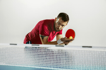 Wall Mural - Innings. Young man plays table tennis on white studio background. Model plays ping pong. Concept of leisure activity, sport, human emotions in gameplay, healthy lifestyle, motion, action, movement.