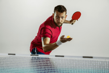 Wall Mural - Answer. Young man plays table tennis on white studio background. Model plays ping pong. Concept of leisure activity, sport, human emotions in gameplay, healthy lifestyle, motion, action, movement.