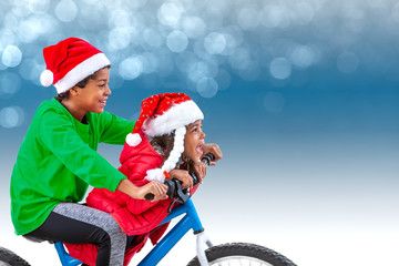 Christmas image of a boy and girl, riding his bicycle weaing Santa's hat, over a blue light bokeh.