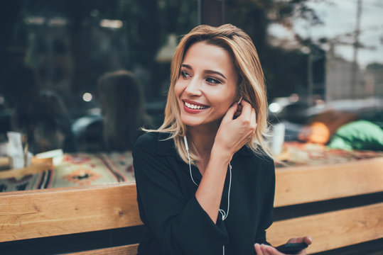 Happy young cute girl with beaming smile listening music in electronic headphones while taking rest on bench in city, positive cheerful female meloman enjoying audio songs from online playlist