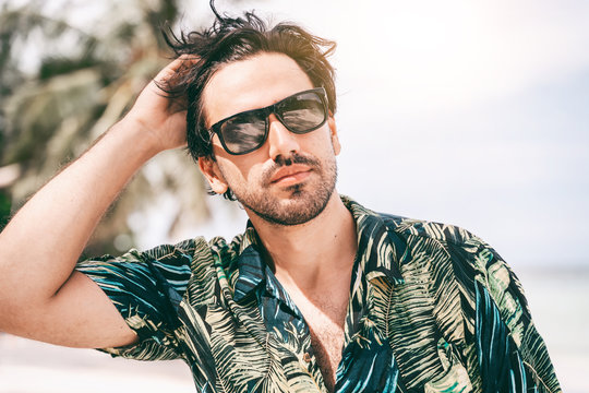 Stylish sexy young brunette man with a beard in a Hawaiian shirt, portrait on a tropical beach