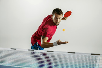 Wall Mural - Power. Young man plays table tennis on white studio background. Model plays ping pong. Concept of leisure activity, sport, human emotions in gameplay, healthy lifestyle, motion, action, movement.