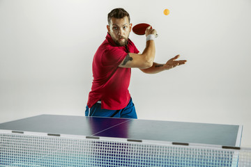 Wall Mural - Overcoming. Young man plays table tennis on white studio background. Model plays ping pong. Concept of leisure activity, sport, human emotions in gameplay, healthy lifestyle, motion, action, movement.
