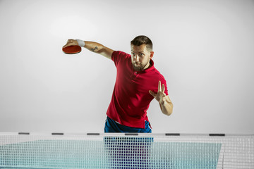 Wall Mural - Thirst. Young man plays table tennis on white studio background. Model plays ping pong. Concept of leisure activity, sport, human emotions in gameplay, healthy lifestyle, motion, action, movement.