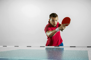 Wall Mural - Moment. Young man plays table tennis on white studio background. Model plays ping pong. Concept of leisure activity, sport, human emotions in gameplay, healthy lifestyle, motion, action, movement.