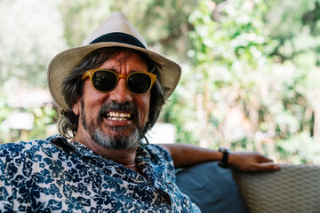 Man with a hat and sunglasses smiling at camera leaning on a sofa