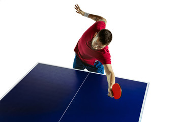 Wall Mural - Looking for. Young man plays table tennis on white studio background. Model plays ping pong. Concept of leisure activity, sport, human emotions in gameplay, healthy lifestyle, motion, action, movement