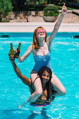 Vertical photo of a girl sitting on the shoulders of a black boy with dreadlocks toasting with beer and pointing to the sky
