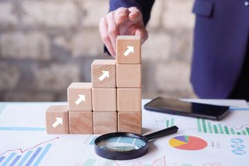Business concept growth success process, man hand arranging wood block stacking on paper chart closeup.
