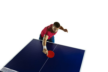 Wall Mural - Attented. Young man plays table tennis on white studio background. Model plays ping pong. Concept of leisure activity, sport, human emotions in gameplay, healthy lifestyle, motion, action, movement.