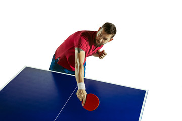 Wall Mural - Amazed. Young man plays table tennis on white studio background. Model plays ping pong. Concept of leisure activity, sport, human emotions in gameplay, healthy lifestyle, motion, action, movement.