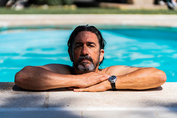 Man leaning his arms on the edge of a pool with wet hair and wearing a watch