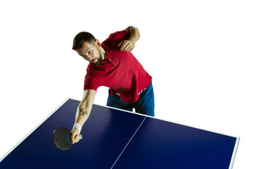 Wall Mural - Excited. Young man plays table tennis on white studio background. Model plays ping pong. Concept of leisure activity, sport, human emotions in gameplay, healthy lifestyle, motion, action, movement.