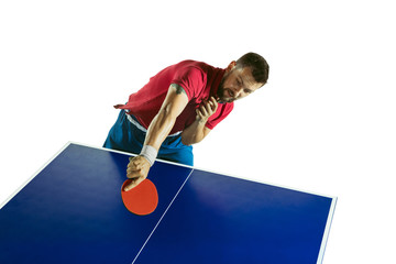 Wall Mural - Tense. Young man plays table tennis on white studio background. Model plays ping pong. Concept of leisure activity, sport, human emotions in gameplay, healthy lifestyle, motion, action, movement.