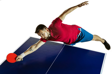 Wall Mural - Strained. Young man plays table tennis on white studio background. Model plays ping pong. Concept of leisure activity, sport, human emotions in gameplay, healthy lifestyle, motion, action, movement.