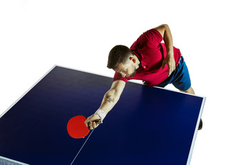 Wall Mural - Strenuous. Young man plays table tennis on white studio background. Model plays ping pong. Concept of leisure activity, sport, human emotions in gameplay, healthy lifestyle, motion, action, movement.