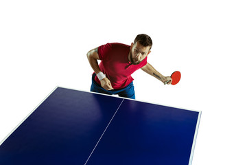Wall Mural - Eager. Young man plays table tennis on white studio background. Model plays ping pong. Concept of leisure activity, sport, human emotions in gameplay, healthy lifestyle, motion, action, movement.
