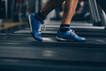 close up of man feet running on treadmill in the gym. concept of doing sport, healthy living,...
