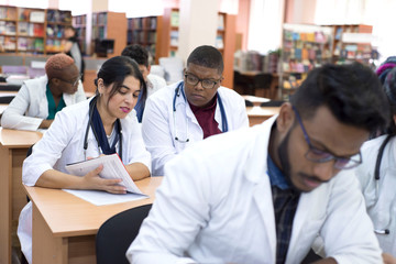 Multinational group of young students at a medical university studying medical journals while sitting at a table in a classroom