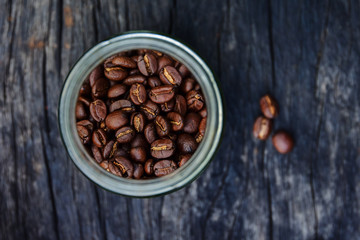 roasted coffee beans in glass containers on old wood table background, overhead view with copy space