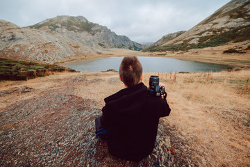 Stock photo of girl sitting in front of a lake surrounded by mountains with a camera in his hands. Nature and travel