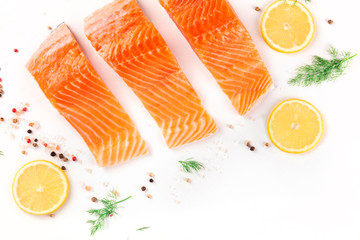 Slices of salmon with lemon and dill, shot from above with salt and pepper on a white background with a place for text. Cooking fish, a flat lay composition