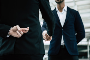Businessman or politician cross finger, hiding behind his back during he get handshake to another person, businessman. Businessman pretend to be good person, he is liar. White collar worker is fraud - fototapety na wymiar