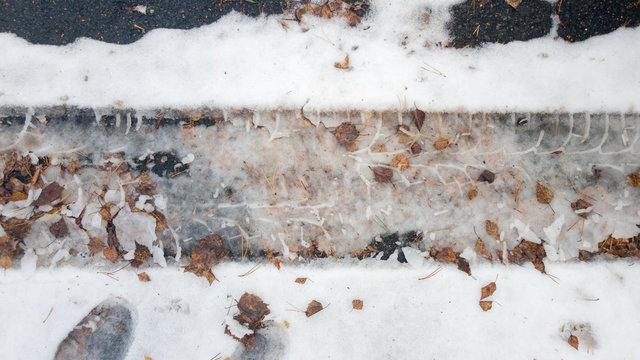 Tire tracks in the melting snow on asphalt road