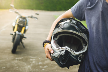 Biker man in shirt vintage is holding a helmet and modern motorcycle blur background. Biker. Biker...