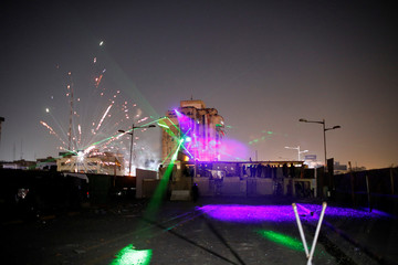 Iraqi demonstrators use firework and laser during the ongoing anti-government protests in Baghdad