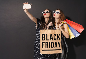 Image of girls taking selfie on cellphones and holding black friday bag
