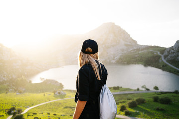 A beautiful caucasian blond woman in front of the camera wearing casual clothes in a mountainous landscape with lake