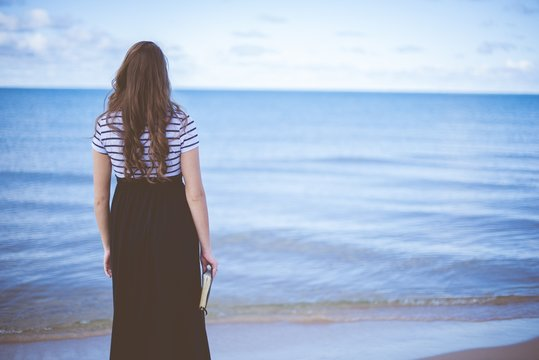 Female standing on beach shore while holding the bible with blurred background shot from behind