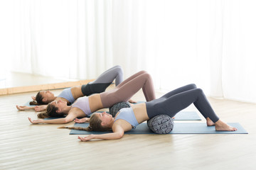 Restorative yoga with a bolster. Group of three young sporty attractive women in yoga studio, lying...