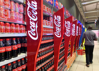A man walks past shelves of Coca-Cola bottles and cans at a Shoprite store inside Palms shopping mall in Lagos