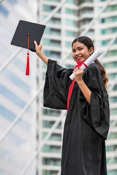 A female Asian student in graduation gown holding the diploma and graduation cap