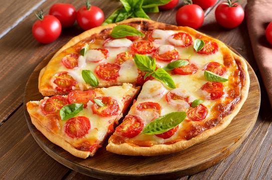 Sliced pizza Margarita on wooden table