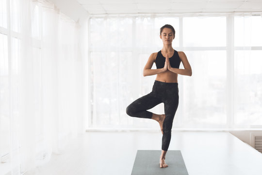 Finding right balance. Woman doing perfect tree pose