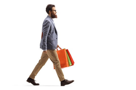 Bearded man walking and carrying shopping bags