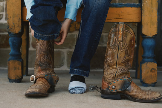 Woman putting cowboy boots on close up for work.