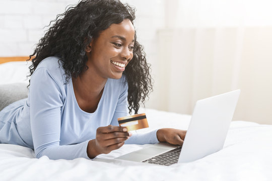 Happy black woman making online purchases from home
