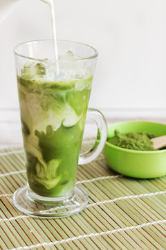 Iced matcha latte drink in tumbler glass with coconut milk pouring from pitcher by hand, copy space.