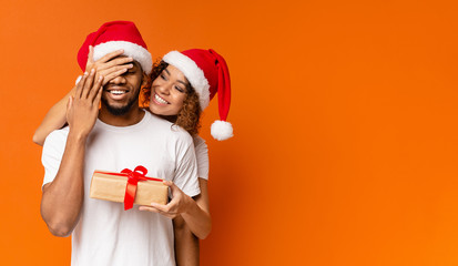 Black millennial couple with Christmas gift on orange background