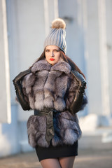 Woman in fur coat, black leather gloves, gray hat