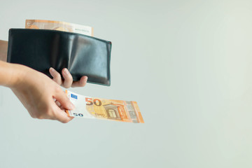 A hand picking a banknote from the short wallet and paying in EURO currency.