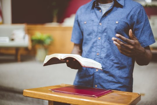 Closeup shot of a male reading the bible near a wooden stand with a blurred background